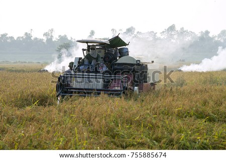 HAI DUONG, VIET NAM, 15 November 2017. Farmer in rural Hai Duong, Vietnam, in the harvest of wet rice. People use the industrial reaper #755885674