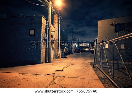 Scary dark city Chicago alley next to an urban warehouse and parking lot. Royalty-Free Stock Photo #755895940