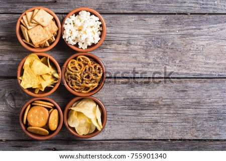 Mix of snacks : pretzels  crackers  chips  nuts  popcorn and nachos Royalty-Free Stock Photo #755901340