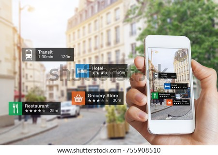 Augmented Reality (AR) information technology about nearby businesses and services on smartphone screen guide customer or tourist in the city, close-up of hand holding mobile phone, blurred street #755908510
