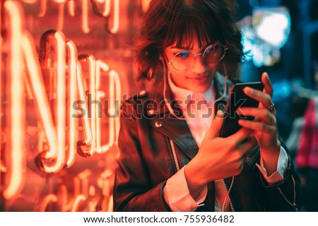 Young stylish female hipster standing near neon red light in night city and listening to music in headphones on modern smartphone. Woman watching media video on cellphone device Royalty-Free Stock Photo #755936482