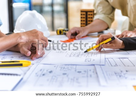Image of team engineer checks construction blueprints on new project with engineering tools at desk in office. Royalty-Free Stock Photo #755992927