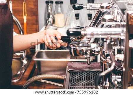 Women Barista using coffee machine for making coffee in the cafe #755996182