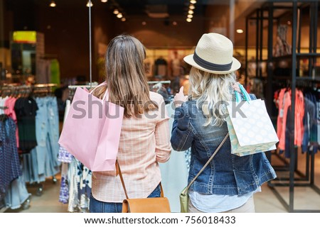 Two women shopping as customers in front of a retail boutique #756018433
