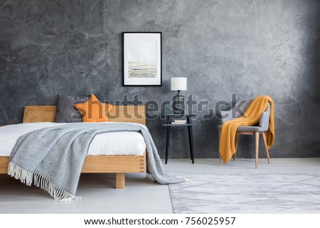 Orange blanket on chair in dark bedroom with poster above lamp on stool and king-size bed #756025957