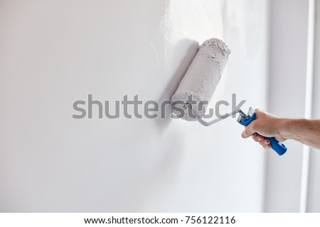 Male hand painting wall with paint roller. Painting apartment, renovating with white color paint Royalty-Free Stock Photo #756122116