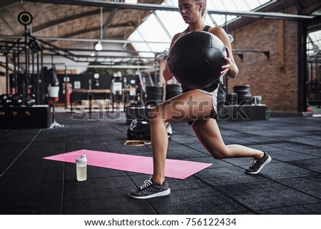 Fit young blonde woman in sportswear working out alone in a gym doing core exercises with a swiss ball  #756122434