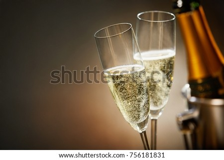 Two romantic glasses of sparkling champagne alongside a bottle in an ice bucket and copy space to celebrate a wedding, anniversary, New Year or Valentines day Royalty-Free Stock Photo #756181831