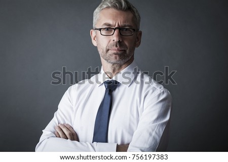 Closeup portrait of businessman looks through glasses at us on gray background #756197383