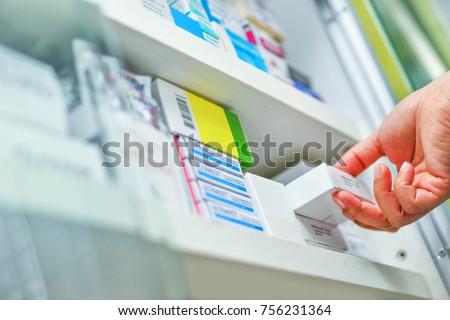 Closeup pharmacist hand holding medicine box in pharmacy drugstore. Royalty-Free Stock Photo #756231364