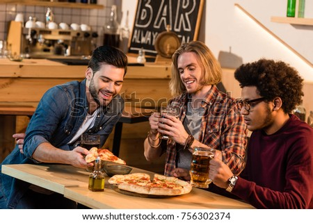 happy young multiethnic friends drinking beer together in bar  #756302374