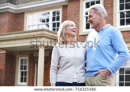 Smiling Mature Couple Standing Outside Home #756325186