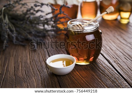 Honey in jar with honey dipper on wooden background #756449218