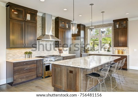 Luxury kitchen accented with large granite kitchen island, taupe tile backsplash, natural brown wood cabinets and lots of natural light. Northwest, USA #756481156