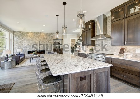 Luxury kitchen accented with large granite kitchen island, taupe tile backsplash, natural brown wood cabinets and high-end stainless steel appliances. Northwest, USA #756481168