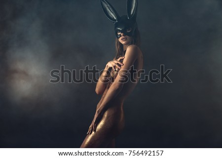Beautiful naked woman in fashion bunny mask. Body covered with gold glitter #756492157