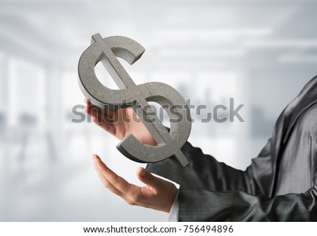 Closeup of business woman in black suit keeping stone dollar sign in hands with office view on background. Mixed media. #756494896
