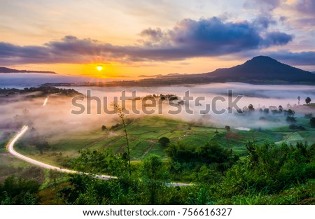 Scenery view of sunrise with mist and traffic trails from Khao Ta-Khian Ngo Viewpoint. Location in Khao Kho District, Phetchabun, Thailand, Southeast Asia. Royalty-Free Stock Photo #756616327