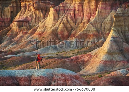A person taking pictures in colorful striped Mongolian canyons Tsagaan Suvarga. photographer takes photo of a bright beautiful canyon.