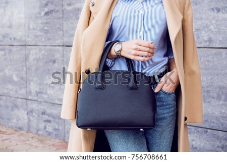 Autumn trendy outfit woman in stylish beige coat and jeans with black big bag Royalty-Free Stock Photo #756708661