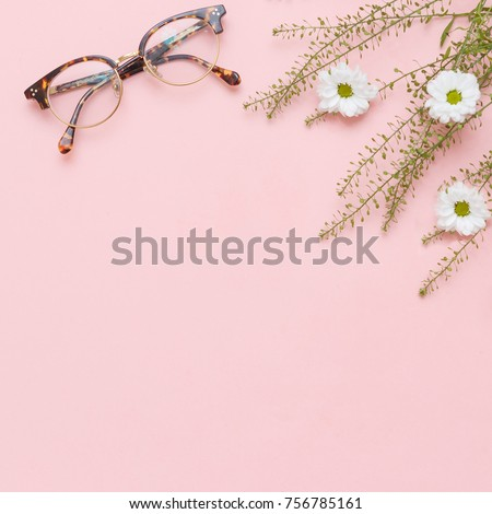 Flat lay of girls stuff like rings, perfume, flowers and eyeglasses on pink pepper and white marble background