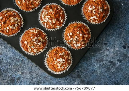 Carrot cake muffins with nuts, raisins and oats on a blue stone background. #756789877
