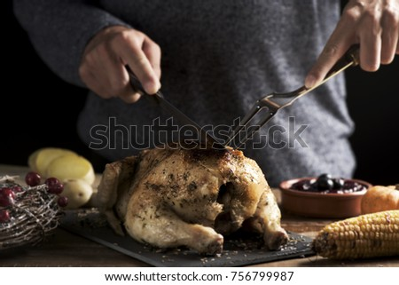 closeup of a young caucasian man young man carving a roast turkey placed on a rustic wooden table next to some slices of roasted potatoes or a roast corn on the cob #756799987