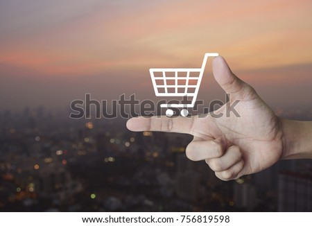 Shopping cart icon on finger over blur of cityscape on warm light sundown, Shop online concept #756819598