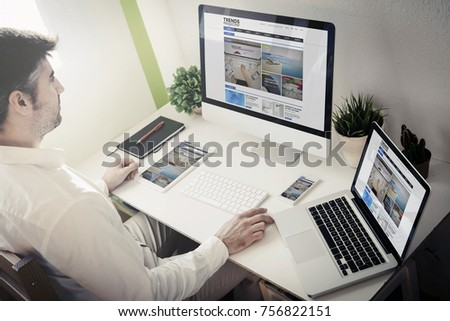 man surfing internet with devices with blog magazine website. All screen graphics are made up. #756822151