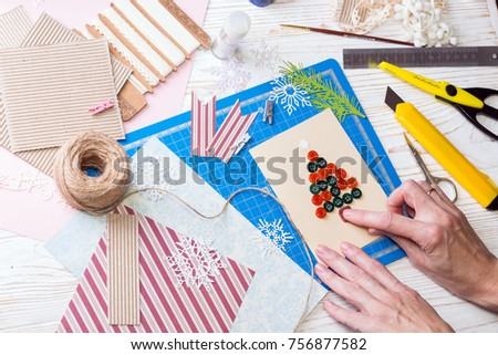 scrapbook background. Girl make christmas postcard from buttons and tools with decoration  #756877582