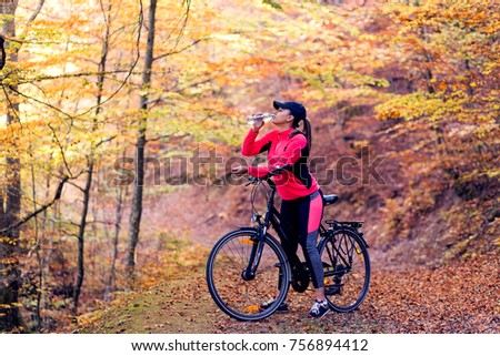 Pretty woman on bicycle in the park #756894412