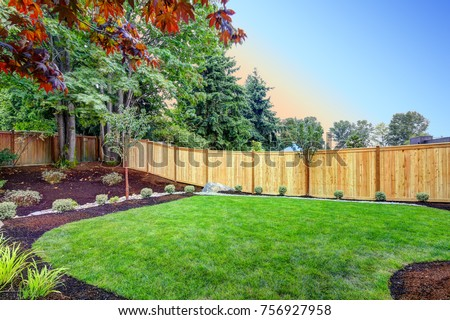 View of an attractive backyard with new planting beds and well kept lawn. Northwest, USA Royalty-Free Stock Photo #756927958