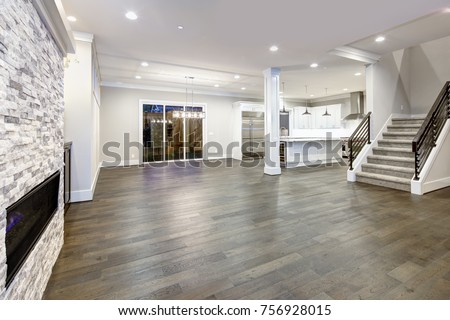 Interior columns separate kitchen from living room with stone fireplace, gray hardwood floor and modern staircase. Northwest, USA.  Royalty-Free Stock Photo #756928015