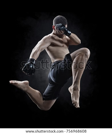 mma male fighter jumping with a knee kick Royalty-Free Stock Photo #756968608