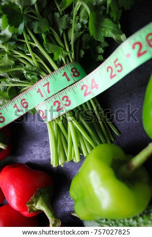 Fresh organic parsley,tomatoes,red peppers,green peppers,fennel,dill and cucumber with green centimeter on black background.top view,diet concept #757027825