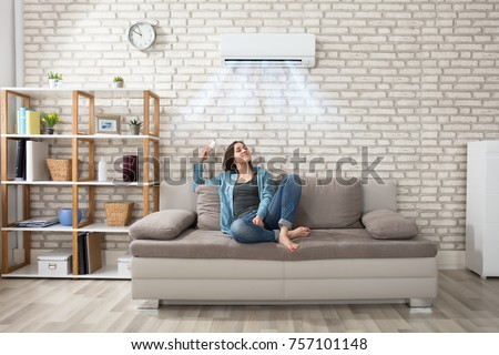 Happy Young Woman Holding Remote Control Relaxing Under The Air Conditioner #757101148