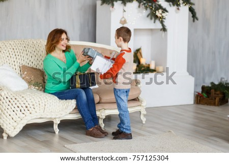 A mother and a son with christmas presents in front of the fur-tree with candles. New year's eve. Christmas eve. Cozy holiday at the fir-tree with lights and gold decor. #757125304