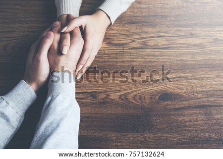 Closeup on two young lovers holding hands at a table #757132624