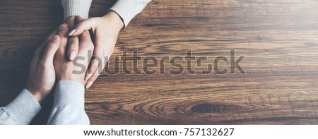 Closeup on two young lovers holding hands at a table #757132627