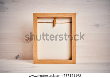 Old empty frame on a shelf on a wooden background #757141192