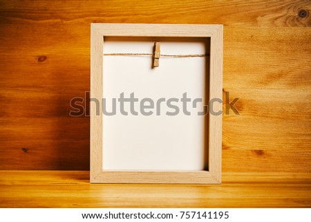 Old empty frame on a shelf on a wooden background #757141195