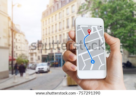 Tourist using GPS map navigation app on smartphone screen to get direction to destination address in the city streets, travel and technology #757291390
