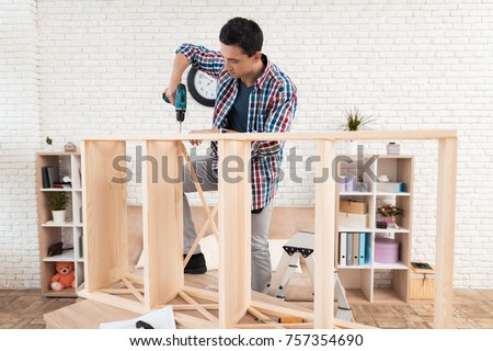 The young man tries himself to fold his bookcase. He uses tools for furniture. He will use this furniture for the interior of his room. #757354690