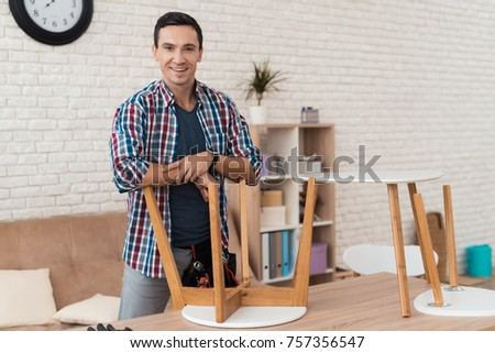 The young man tries himself to fold his coffee table and stools. He uses tools for furniture. He will use this furniture for the interior of his room. #757356547