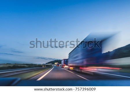 Background photograph of a highway, trucks on a highway, motion blur, light trails. Evening or night shot of trucks doing transportation and logistics on a highway. #757396009