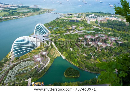 Singapore - November 11, 2017 : Skyline view of the Singapore Gardens by the bay, Flower dome and Cloud Forest facing the Ocean. A view of Gardens by the bay from Marina bay sands observation deck  #757463971