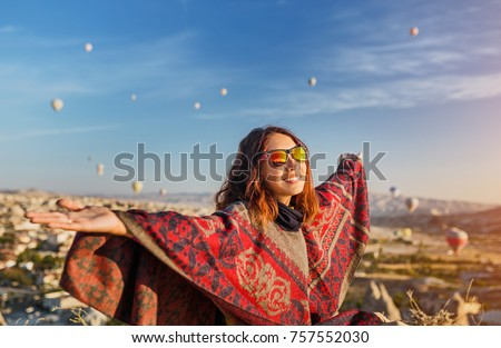 A tourist girl on a mountain top enjoying wonderful view of the sunrise and balloons in Cappadocia. Happy Travel in Turkey concept #757552030
