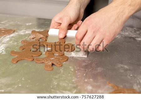 Baker picking up gingerbread man shaped raw gingerbreads for being bake in owen  #757627288