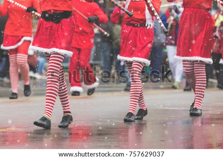 Marchers in a Christmas parade wearing striped tights #757629037