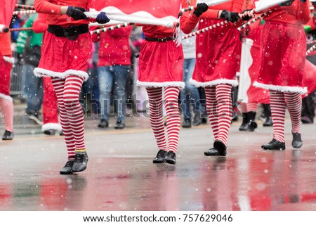 Marchers in a Christmas parade wearing striped tights #757629046